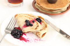 Pancakes on a plate with black currant jam Stock Photos