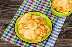 Pancakes in plate and bowl on checkered towel on table Stock Images