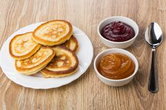 Pancakes in plate, bowls with apricot and raspberry jam, teaspoo Royalty Free Stock Photo