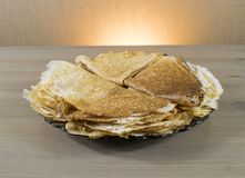 Pancakes on a plate on a brown table royalty free stock photos