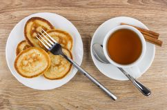 Pancakes in plate, fork, tea, cinnamon sticks and teaspoon Stock Photography