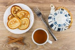 Pancakes in plate, fork, teapot, cinnamon sticks and tea Royalty Free Stock Photos