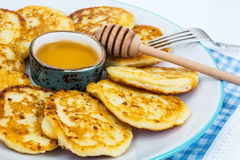 Pancakes on plate and honey in small bowl Royalty Free Stock Photo