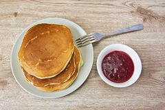Pancakes on a plate and jam in a white сup. On the plate Stock Images