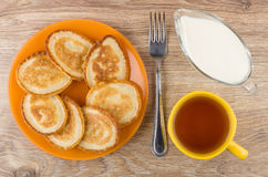 Pancakes in plate, jug of sour cream, tea and fork. On wooden table. Top view Stock Photography