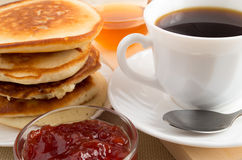 Pancakes on a plate next to the strawberry jam, honey and a cup Stock Photo