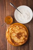 Pancakes on a plate with sour cream and honey. Homemade pancakes on a plate with sour cream and honey on wood table Royalty Free Stock Photography