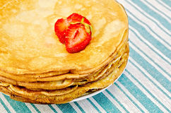 Pancakes on a plate with strawberries on a napkin Stock Photos