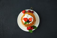 Pancakes in a plate with strawberries, whipped cream, mint, honey and cherry on a dark black background. stock images