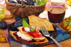 Pancakes with plum confiture and whipped cream Stock Photos