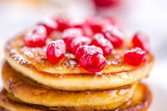 Pancakes with pomegranate seeds, honey and powdered sugar stock photography