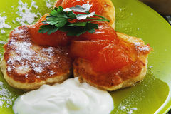 Pancakes with powder, cream and apricot jam on a plate. Royalty Free Stock Image