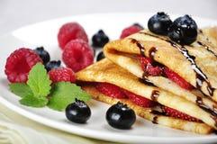 Pancakes with raspberries. Pancakes sereved with raspberries, blueberries and chokolate on plate. Shallow dof Stock Image