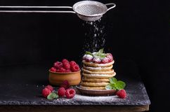 Pancakes with raspberries and berries around. On black backgound Royalty Free Stock Photography