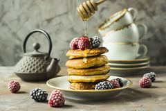 Pancakes with raspberries and blackberries. Honey pours on the drain of pancakes on a plate with raspberries and blackberries next to cups and a kettle on a gray Royalty Free Stock Photos
