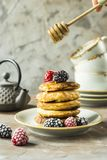 Pancakes with raspberries and blackberries. Honey pours on the drain of pancakes on a plate with raspberries and blackberries next to cups and a kettle on a gray Stock Photos