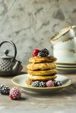 Pancakes with raspberries and blackberries. A pile of pancakes on a plate with raspberries and blackberries next to cups and a kettle on a gray table. Summer Royalty Free Stock Photo