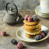Pancakes with raspberries and blackberries. A pile of pancakes on a plate with raspberries and blackberries next to cups and a kettle on a gray table. Summer Stock Images