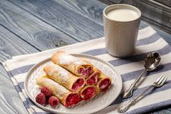 Pancakes with raspberries and a Cup of milk. Berry dessert closeup. Pancakes with raspberry and cream. A Cup of milk. A traditional dish of Russian cuisine. Free Royalty Free Stock Photo