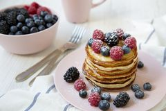 Pancakes with raspberry, blackberry ,blueberry on white wooden table, side view. Closeup Stock Images
