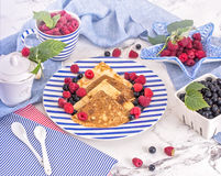 Pancakes with raspberry, currant on blue stripped plate with textile, close-up white marble background Stock Images