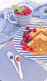 Pancakes with raspberry, currant on blue stripped plate with textile, close-up white marble background Royalty Free Stock Images