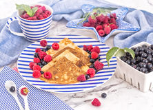 Pancakes with raspberry, currant on blue stripped plate with textile, close-up white marble background. Pancakes with raspberry, currant on blue stripped plate Stock Images
