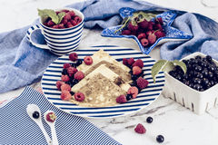 Pancakes with raspberry, currant on blue stripped plate with textile, close-up white marble background royalty free stock image