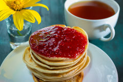 Pancakes with raspberry jam and a cup of tea Royalty Free Stock Images