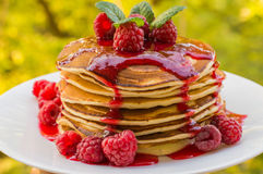 Pancakes with raspberry jam and fresh berries. Wooden background. Close-up Stock Photography
