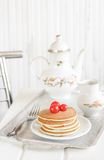 Pancakes with red berries. On the white table royalty free stock photography