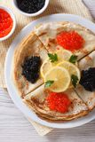 Pancakes with red and black caviar closeup, vertical top view Stock Images