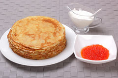 Pancakes, red caviar and sour cream Royalty Free Stock Images