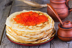 Pancakes with red caviar. On a wooden background royalty free stock photography