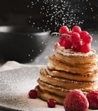 Pancakes with red currant dark powder sugar front royalty free stock photo