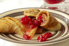 Pancakes with red currant jam on plate Royalty Free Stock Image