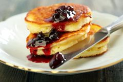 Pancakes with ricotta and cowberry sauce. Stock Images