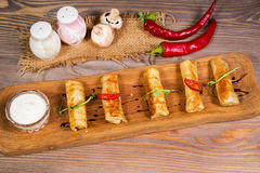 Pancakes rolls with chicken. And mushrooms on wooden plate Stock Images