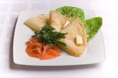 Pancakes with salty salmon on white plate Royalty Free Stock Images