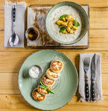 Pancakes with sauce, mint on a green plate, cereal with fruit, tea, cutlery, on a wooden table. View from above Stock Images