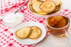 Pancakes on saucer, soft cottage cheese, bowl with pancakes, tea Royalty Free Stock Images