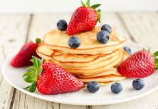 Pancakes served with berries. Pancakes served with blueberries,strawberries and maple syrup Royalty Free Stock Image