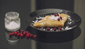 The pancakes are served on a black plate on a black background Royalty Free Stock Image
