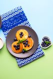 Pancakes served with blueberries on gray plate. Pancakes served with fresh blueberries on gray plate over geometrical background. Healthy home made breakfast royalty free stock image