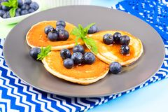 Pancakes served with blueberries on gray plate. Pancakes served with fresh blueberries on gray plate over geometrical background. Healthy home made breakfast royalty free stock images
