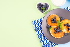 Pancakes served with blueberries on gray plate. Pancakes served with fresh blueberries on gray plate over geometrical background. Healthy home made breakfast stock photo