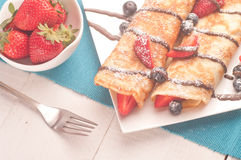 Pancakes served with strawberries, blueberries and chocolate Stock Photos
