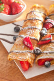 Pancakes served with strawberries, blueberries and chocolate Royalty Free Stock Images