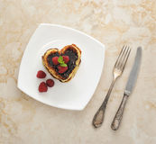 Pancakes in the shape of hearts with raspberries and chocolate Stock Photo