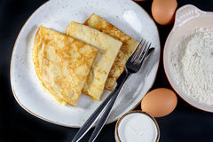 Pancakes on Shrove Tuesday with the ingredients. On a plate on black background with eggs and flour Stock Photos